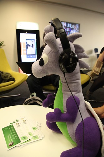 Photo of a toy dragon wearing headphones
