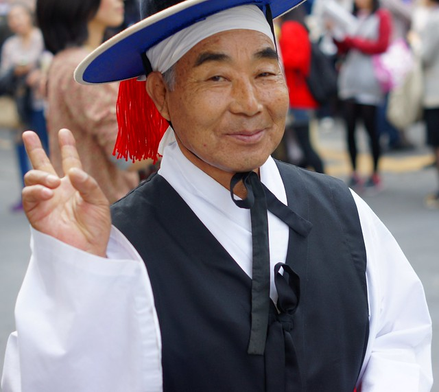 Korean man wearing traditional clothes smiles, image from flickr user Nomadic Samuel
