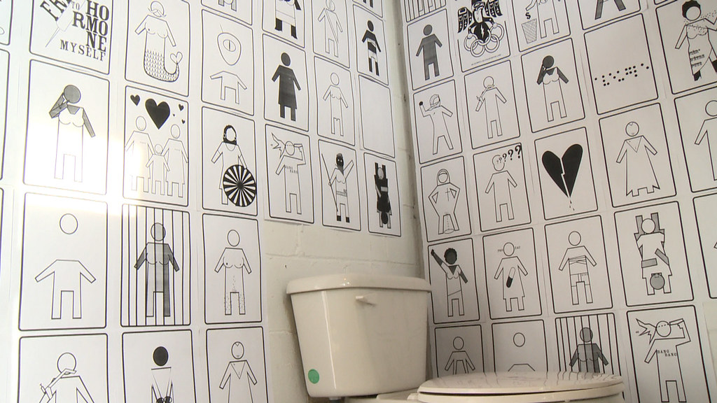 A pic of the intallation Genderpoo. The walls of a restroom are covered with black and white images that on first glance resemble women and men signs. The figures in these pictures are different though, different shades of grey, with gender-bending, and non-normative body types
