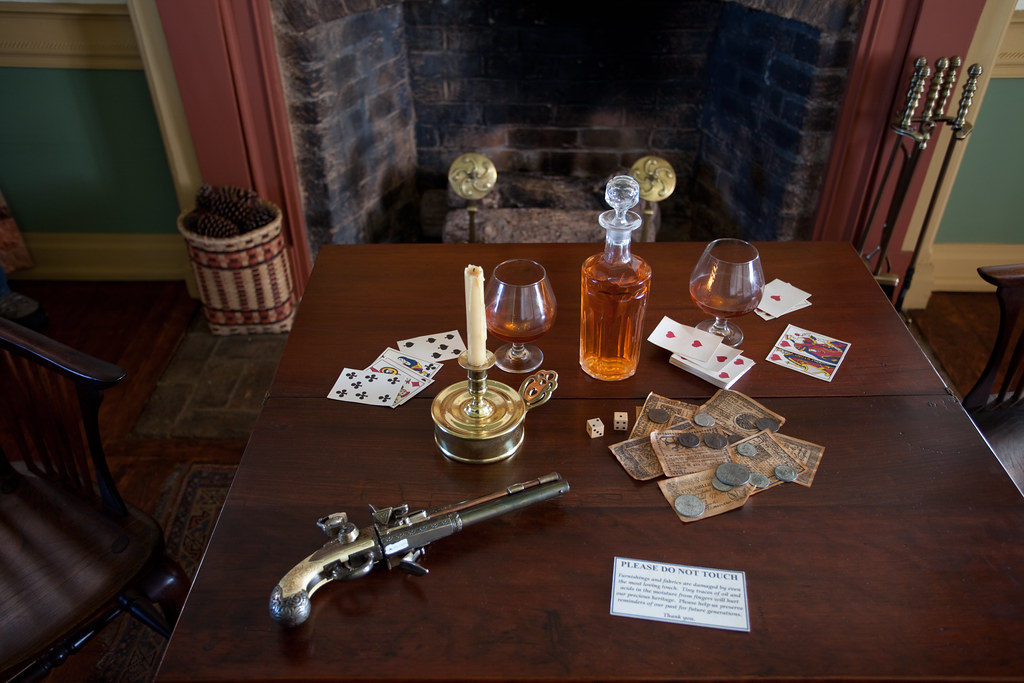 Card table, refreshments, and a weapon on display