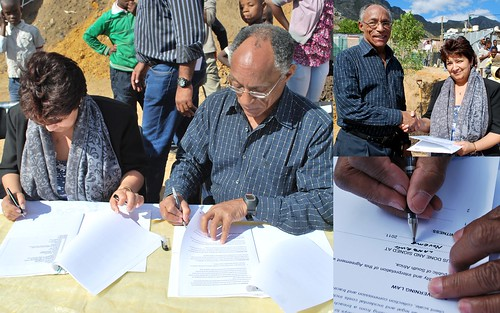 "international delegation, sign sbos </p> <p>New political actors have emerged that are influencing the national upgrading agenda. Among these are the Informal Settlement Network (ISN), a bottom-up agglomeration of local-level and national-level organisations of urban poor in Cape Town, Ekurhuleni, eThekwini (Durban), Johannesburg, Nelson Mandela Bay (Port Elizabeth), and Stellenbosch. ISN, together with the Federation of the Urban Poor (FEDUP) – a woman-led federation of slum dwellers practicing savings, enumerations and partnerships with the state – and support NGOs Community Organisation Resource Centre (CORC), iKayalami, and uTshani Fund, promote pro-poor and inclusive cities through people-centred development. These organisations are linked to Shack/Slum Dwellers International (SDI), a global network of similar organisations of the urban poor in 33 countries across Asia, Africa and Latin America. SDI builds partnerships with government that put shack dwellers at the centre of upgrading their built environment. As the South African SDI Alliance saying goes: ""Nothing for us without us"".</p> <p>The Alliance promotes the establishment of citywide ""Urban Poor Funds"" which are community-driven development funding facilities that support community-initiated projects. Urban Poor Funds are financed by contributions from the local municipality combined with the savings of the poor, and are often strengthened by international donor funding. These funds are co-managed between organised communities and the municipality, and tend to by-pass the red tape and costly bureaucracy of state delivery mechanisms. These precedent-setting funds build on the collective capacity of local savings groups and link local upgrading efforts to wider policy change. This form of development-finance has particularly gained currency in South East Asian countries where institutional innovation, transparency and accountability resulted in empowered communities and significant poverty alleviation. In South Africa, the Community Upgrading Finance Facility (CUFF), located in uTshani Fund, has provided seed capital for more than 50 pilot upgrading projects. Communities are expected to contribute ten percent to the total project cost, a significant contribution considering the depth of poverty in many settlements.</p> <p>Stellenbosch Municipality has been a trend-setter in pledging support and partnership toward such ends. The sheer scale of the housing need – a backlog of 19,701 housing subsidy applications paired with roughly 9,000 backyarder households and 9,000 informal settlement households – compared to the meagre 300 housing subsidy allocations per year, illustrates the extent of the urban crisis Stellenbosch Municipality is facing. The partnership-in-the-making has evolved over two years and key city officials, such as Mr. David Carolissen (manager of the informal settlements department) and Mr. Johru Robyn (town planner in the housing department), were exposed to upgrading projects in Uganda through the SDI learning exchange programme. ""We were investigating alternative solutions to the problems being faced by shack dwellers and approached SDI about two years ago in the hope that we could not only investigate potential partnerships but also note key lessons learned in managing informal settlements. The involvement of community members is crucial in achieving any form of success and partnering with SDI cements this involvement,"