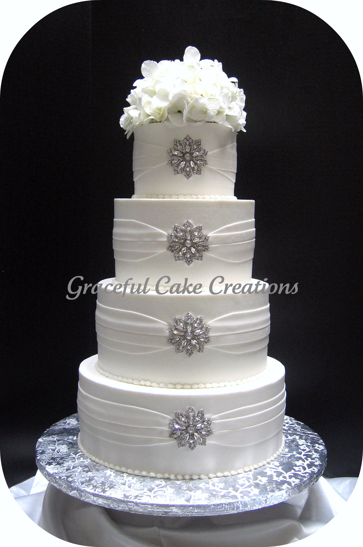 Elegant White Wedding Cake with Silver Brooches