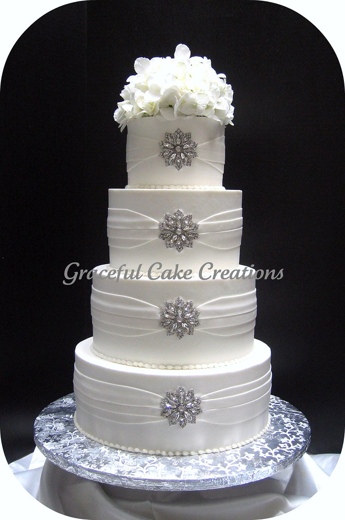 Elegant White Wedding Cake With Silver Brooches A Photo On