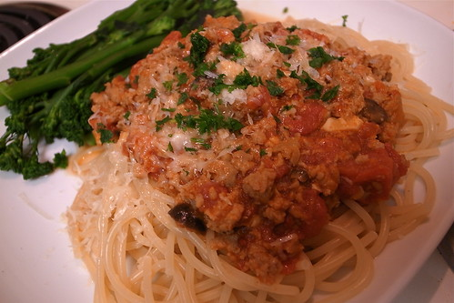 Spaghetti Bolognese with Spicy Sausage, Black Olives, and Roasted Garlic, a side of crisply boiled broccolini