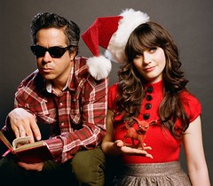 Zooey Deschanel and M Ward in a promo shoot for their holiday album. She is wearing a santa hat and he is reading a book.