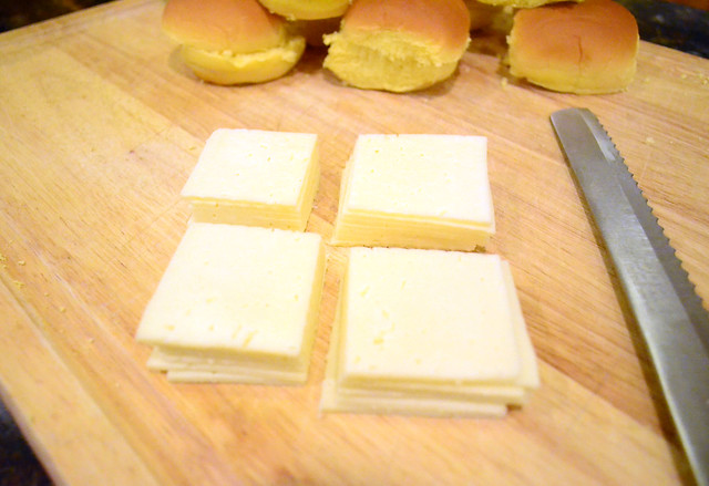 A pile of 6 slices of Havarti cheese that has been cut into qaurters.