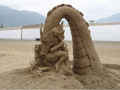 sandcastle dragon consuming a person with a shovel