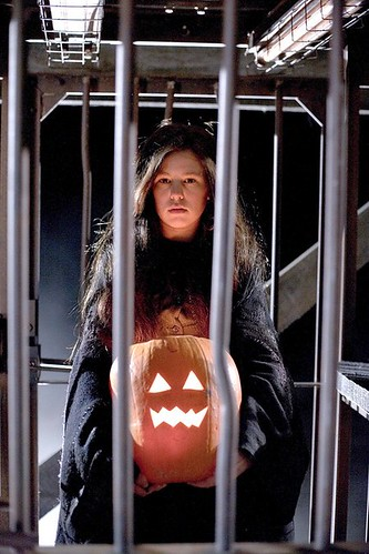 white woman with long brown hair wears a black robe and holds a lit jackolantern. She is in a cage.