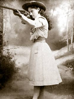 A photo of Annie Oakley holding a long rifle.