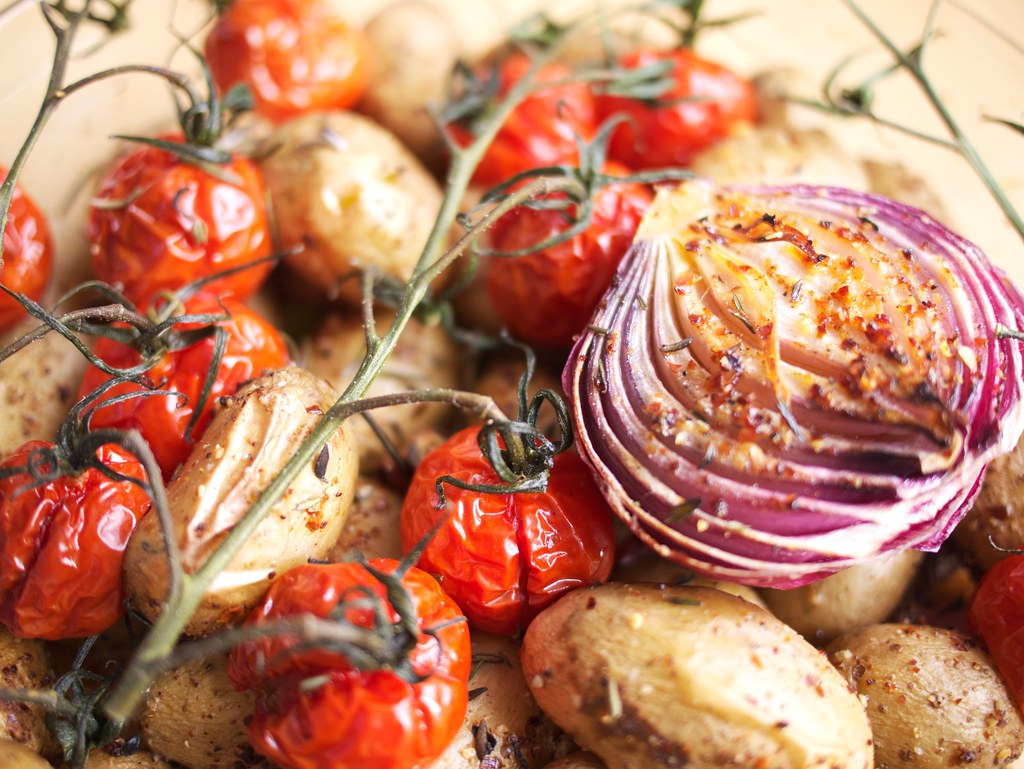 Slow roast new potatoes with cherry tomatoes and red onions