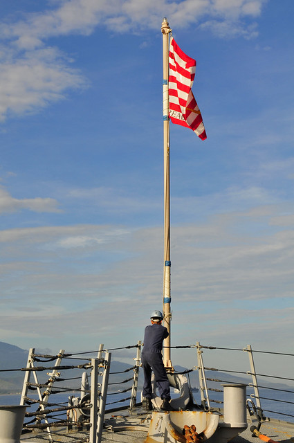 A Sailor aboard USS Stethem (DDG 63) raises the jack of the United States off the coast of Timor-Leste.