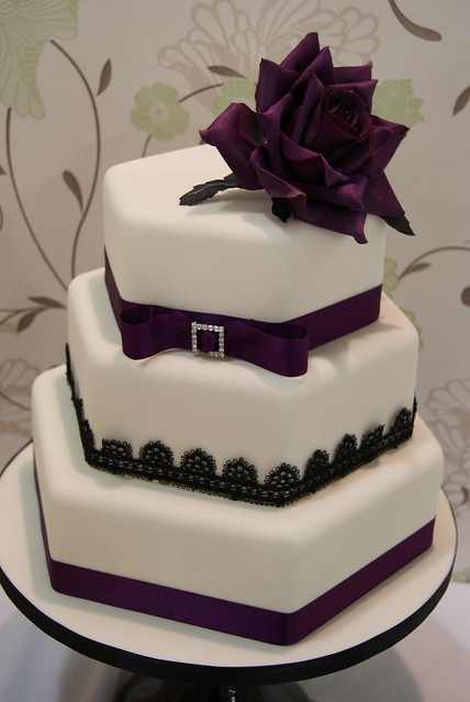 Stacked hexagon shaped cakes trimmed with deep purple ribbon and black lace