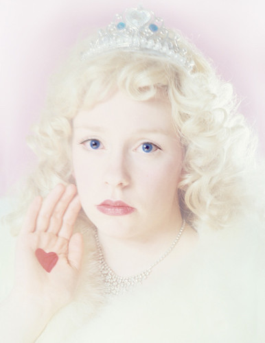 one of the girls as jonbenet ramsay wearing a wig and tiara and looking at the camera