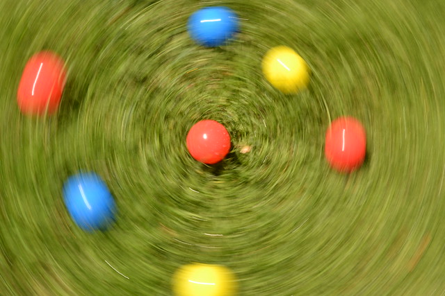 A photo where the movement of the camera creates an interesting blur effect - Coloured balls on grass