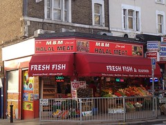 "A corner shop with an open frontage and red framework and canopy.  A display of vegetables outside includes signs offering puna yams at £2.99 (or 2 for £5).  The sign above reads ""M.B.M Halal Meat"" and the canopy reads ""Fresh Fish & Seafood / Jamaican Food / African Food / Yellow Lroaker [sic] / Red Fish / Prawns / Tilapil [sic] / Crab / Mackerel & Vegtab[...] [sic]""."