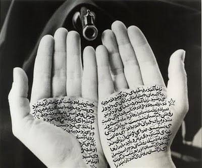 a pair of hands covered in writing in black ink
