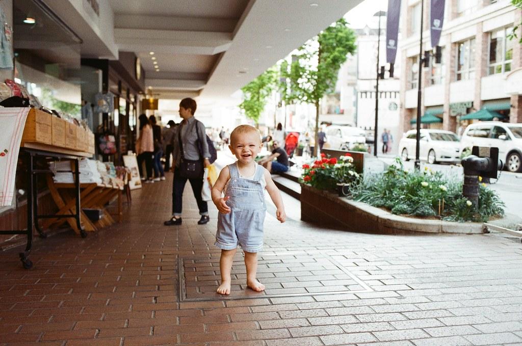 橫濱 Japan / Kodak ColorPlus / Nikon FM2 2016/05/21 那時候準備要離開橫濱,剛好 Lomo LC-A+ 拍完要換底片,我坐在路邊整理,看到一個外國小朋友很高興的跑過來,我趕緊把還有底片的 Nikon FM2 拿起來拍。  很可愛的是他看到我在拍,就在原地大笑起來,我按了好幾張!  後方坐在階梯上的是他爸爸,後來他有點高興過頭,準備要衝向馬路,我和他爸同時衝過去抓住他,哈哈!  Nikon FM2 Nikon AI AF Nikkor 35mm F/2D Kodak ColorPlus ISO200 6412-0012 アメリカ山公園 Photo by Toomore