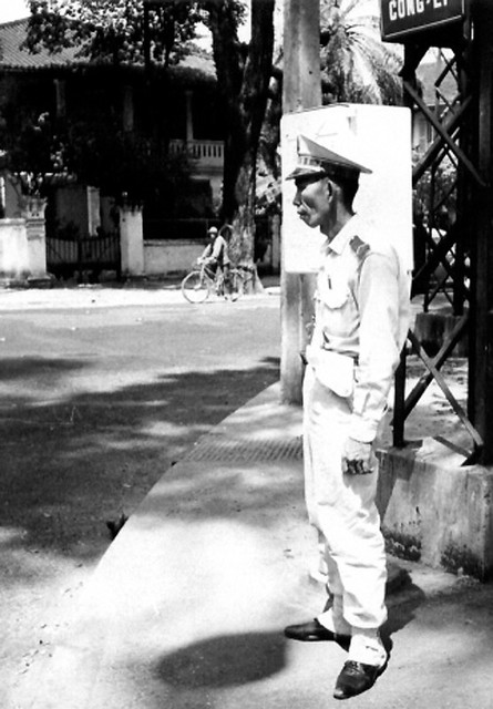 View of a Vietnamese man in uniform on a sidewalk in a city