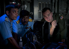 INDIAN OCEAN (April 10, 2012) Tactical Action Officer Lt. Dan Mitzner, right, discusses Combat Direction Center operations with Indian Navy liaison officers Cmdr. Ajay Daniel Theophilus, center, and Lt. Cmdr. Madhavdas Ravikant, left, aboard the aircraft carrier USS Carl Vinson (CVN 70) during exercise Malabar. (U.S. Navy photo by Mass Communication Specialist 2nd Class James R. Evans)