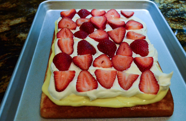 The cake with cool whip evenly spread across the top and strawberries carefully arranged on top of the cool whip.