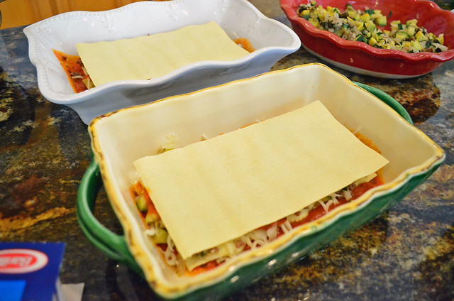 A lasagna sheet added to the top of the partially assembled lasagna.