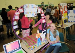 Two students display hula hoops and related information as part of a presentation of the health benefits of hula hoops.