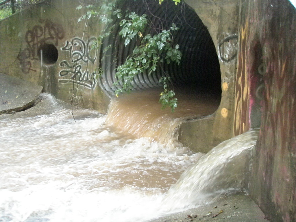 Image of water pouring out of a stormdrain.