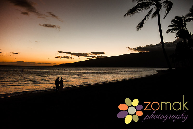Bride and groom walk down the beach during sunset after their maui wedding