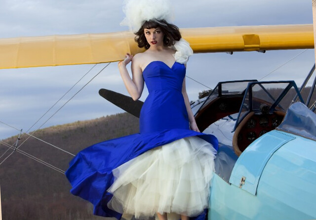 dramatic photo of Kenley in a blue gown by a plane