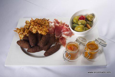 Arañitas de yuca, quipes, jamón ibérico y aceitunas con salsa de ají gustoso picante y salsa de lechosa y ají tití.