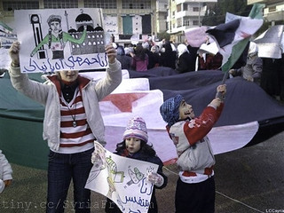 "Young Syrian girls hold Arabic placard read:""I am proud to be Homsi, left, and I am breathing freedom, center,"" during a demostration against the Syrian regime, in Homs"