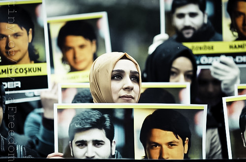 Demonstrators attend a protest against Syria's President Bashar al-Assad as they hold pictures of two Turkish journalists whom activists say are missing in Syria, in front of the Syrian Consulate in Istanbul March 15, 2012.