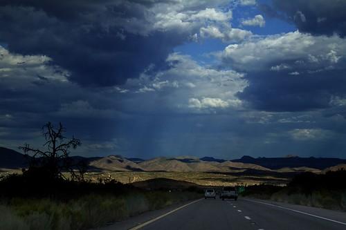 light mountains rain clouds highway driving lasvegas darkclouds nevadadesert grantcanyon