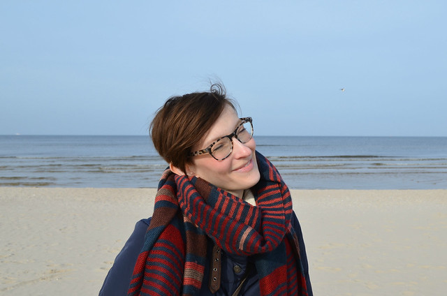 Świnoujście beach Poland_Kate bundled in down coat and Warby Parker Preston glasses in pearled tortoise_closeup