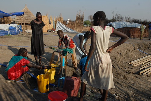 Nyathak Minyjang (with black dress), one of South Sudanese asylum seekers, comes to the water point at least three times a day.