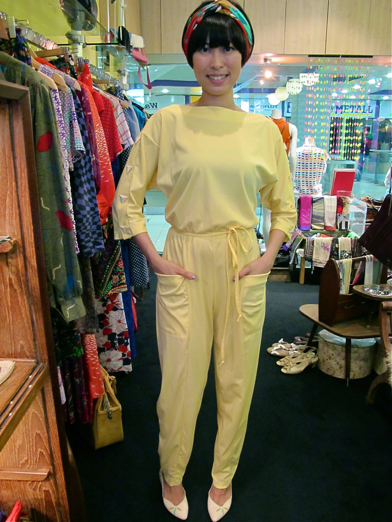 X-Wen wears a 1970s yellow jumpsuit with big pockets (on her body!), a French silk scarf (on her head!) and 1980s leaf-print pumps (on her feet!).