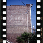 "This is Jump's only photo from Staten Island. The slogan, ""Eventually. Why not now?"" is barely legible on the bottom right, and was supposedly a serendipitous find from the trash of a senior ad man. It was rescued by a young member of the firm who later became the first president of General Mills, Inc. The New York mill was built after the one in Minneapolis shut down and is the first to use automatic steel rollers.   Photo by Frank Jump."