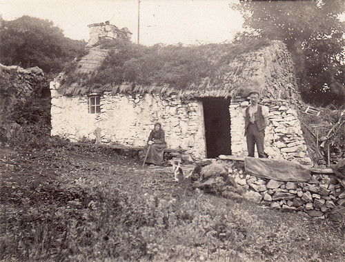 Old couple and a tumbledown whitewashed thatched bothy. Unidentified location. Scotland?