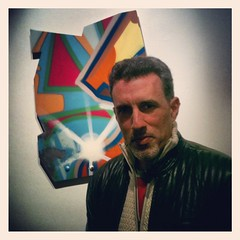 "John Matos, aka CRASH, with one of his spray paint on aluminum works for ""Remnant Memories"""