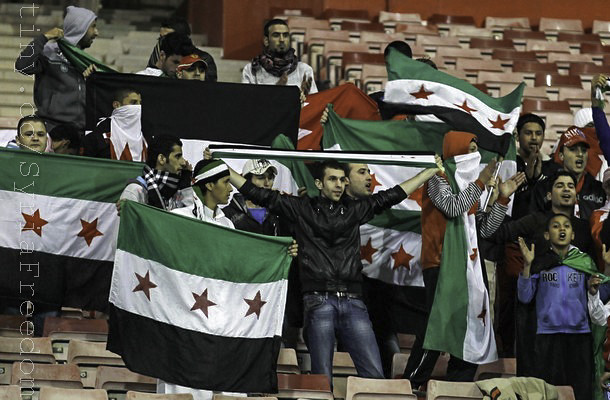 Anti-Assad protesters wave Syrian revolution flags during the London Olympics qualifying soccer match between Syria and Bahrain at Bahrain International Stadium in Isa town, south of Manama