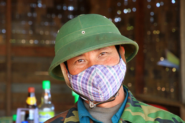 Portrait of a travelling man with a mask in Laos.