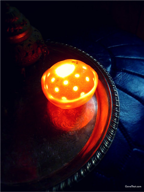 DIY Orange Candle with the lid punched with holes in it on top glowing