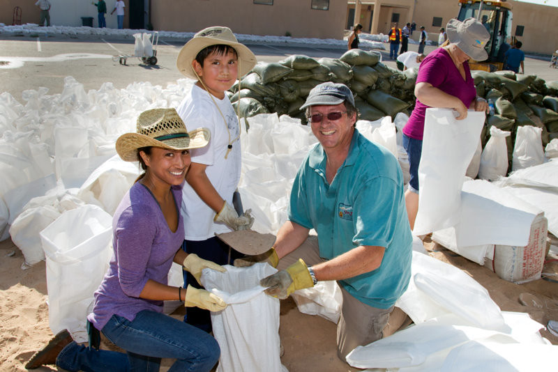Los Alamos National Laboratory employees Cynthia Fuentes, left, and Brian Foley, right, help fill sandbags at Santa Clara Pueblo in 2011. They are assisted by Brenden Baca, 9.