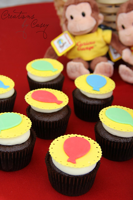 Balloon cupcakes to match the theme of the invitation and party; Curious George