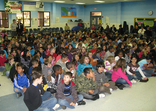 Children listen attentively to the award ceremony.