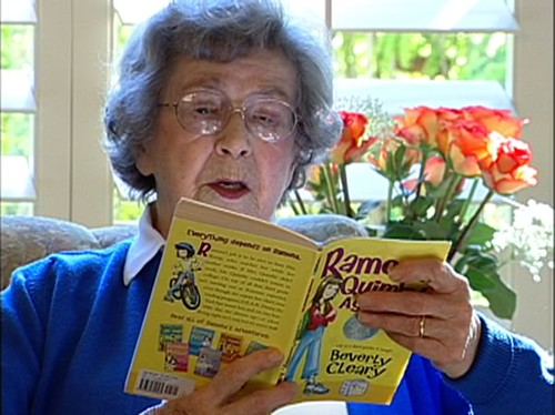 Beverly Cleary, a white woman in a blue sweater, reads from one of her books
