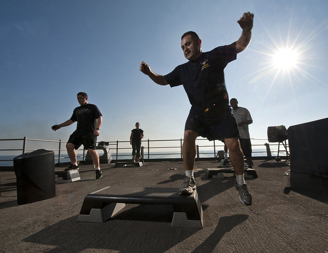 Chief Aircrew Survival Equipmentman Jose Castillo, a fitness instructor, leads a step aerobics class on the fantail of the Nimitz-class aircraft carrier USS Carl Vinson.