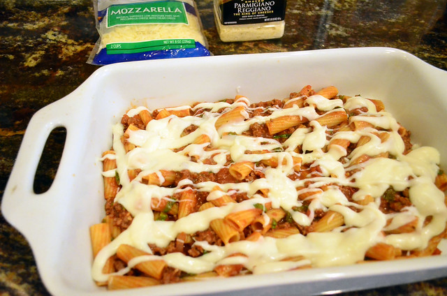 A layer of bechamel is poured over the rigatoni with meat sauce layer.
