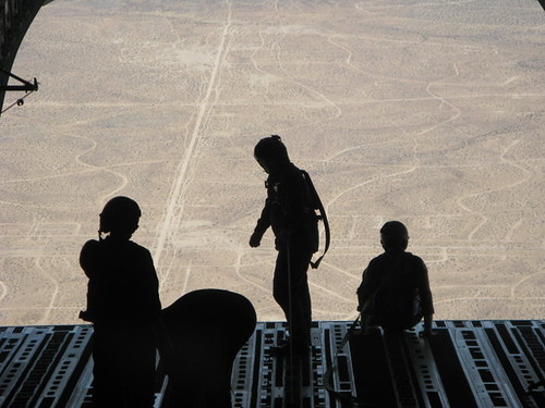 Loadmasters and engineers wear harness during airdrop training with the ramp and door open