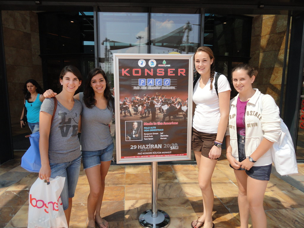 Palo Alto Chamber Orchestra members pose in front of a poster promoting their concert at Pamukkale University Concert Hall in Turkey